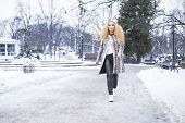 Blonde girl in the park on a winter day