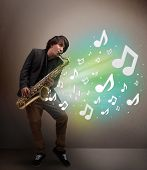 Attractive young musician playing on saxophone while musical notes exploding