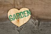 Love Garden Message Wooden Heart Sign On Rough Grey Background