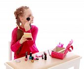 Little girl doing make-up sitting at the table.