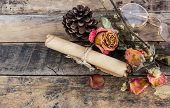 Old Paper Roll, Glasses,and Dry Rose On Wooden