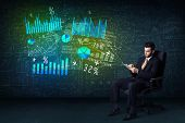 Businessman in office chair with tablet in hand and high tech graph charts concept on background