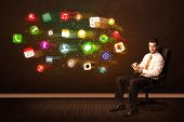 Business man sitting in office chair with tablet and colorful app icons concept on background