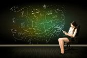 Businesswoman sitting in chair holding tablet with media icons concept on background