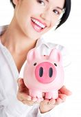 Happy businesswoman holding piggy bank.
