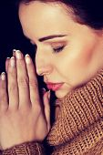 Young woman praying with closed eyes.