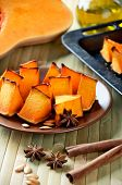 Baked Pumpkin, Cinnamon Sticks, Star Anise And Olive Oil On A Kitchen Table Vertical Closeup