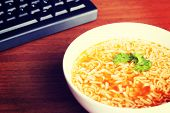 Chinese vegetable pasta soup next to keyboard. Over wooden table.