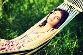 Young woman in cocktail dress relaxing in a hammock on sunny day.