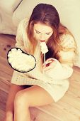 Young depressed woman is eating big bowl of ice creams