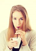 Beautiful woman is drinking from a cup with a straw.