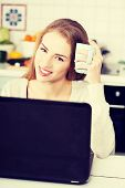 Beautiful woman sitting by the table with laptop and cup.