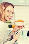 Beautiful caucasian woman holding tablet indoors.