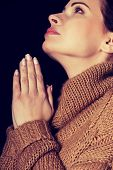 Young woman praying with clenched hands.
