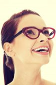 Young beautiful woman in eyeglasses looking up and smiling.