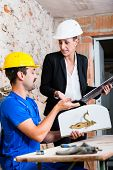 Construction worker and interior designer with door handle discussing door handles