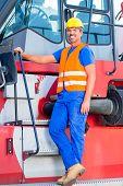 Crane operator standing proud on company yard