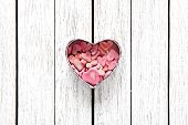 Open heart shaped Valentines Day gift box with heap of small hearts inside on old wooden background.