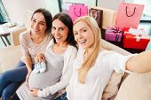 foto of young baby  - Top view of happy young pregnant woman holding baby booties on her abdomen and smiling while two friends sitting close to her and making selfie - JPG
