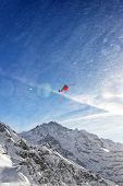 Red Helicopter In Flight In Winter Alps With Snow Powder Streams