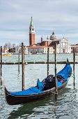 Gondola moored by Saint Mark square with church in the background