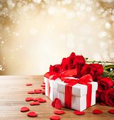 Valentines concept with bouquet of roses and wrapped gift on wooden table