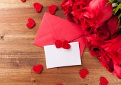 Bouquet of roses with envelope and blank wish card on wooden desk