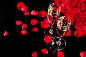 Bouquet of roses with two glasses of champagne, isolated on black background