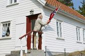 Man fixes national flag at his house in Skudeneshavn, Norway.