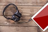Tablet computer with headphones against wooden background