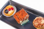 Top Of View Of Delicious Tiramisu Cake Near Little Cakes