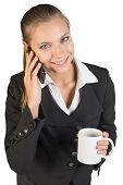 Businesswoman holding mug, talking on the phone