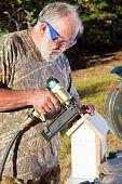Senior Man Building A Bird House