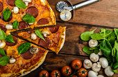 stock photo of salami  - Rustic pizza with salami mozzarella and spinach on a clay plate - JPG