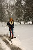 picture of snow shovel  - A young woman shoveling snow off the driveway like a plow - JPG