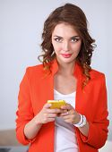 Beautiful businesswoman using cell phone standing in office, isolated