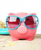 Piggy bank with sunglasses on sand, on white background