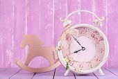 Beautiful vintage clock with decorative horse on table on wooden background