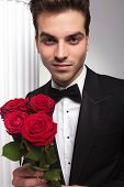 Elegant business man smiling at the camera while holding a bouquet of red roses in his hand