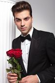 Handsome business man leaning on a white column while holding red roses in his hand, looking at the camera.