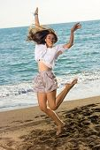 Happy Woman In Jump Shot At The Beach