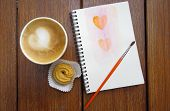cup of coffee with cookie and painting of heart