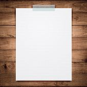 Empty white paper sheet stick on wood background.