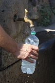Detail Of An Arm While Filling Water In A Plastic Bottle At The Fountain