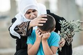 Arabic Muslim Middle Eastern woman with olive branch and son crying