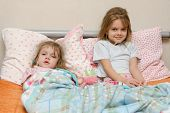 Two Girls Sick In Bed With A Thermometer