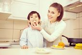 Mother and son preparing food in kitchen together