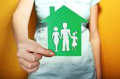 Cutout house with paper family in female hand on colorful background