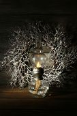 Kerosene lamp with wreath on rustic wooden planks background