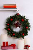 Christmas decoration with wreath on shelf on white wall background